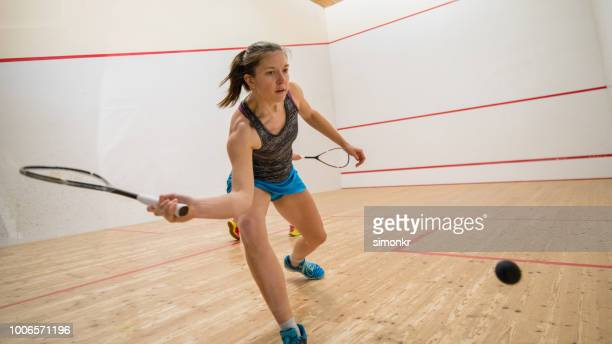 Young woman playing squash game