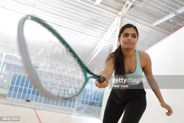 Young woman playing squash