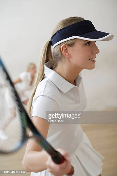 Young woman playing squash, smiling, portrait