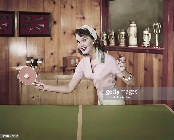 young woman playing table tennis, smiling, portrait - 1950 stockfoto's en -beelden
