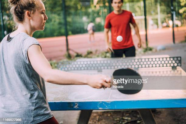 young woman playing table tennis with friend at sports venue - table tennis stock pictures, royalty-free photos & images
