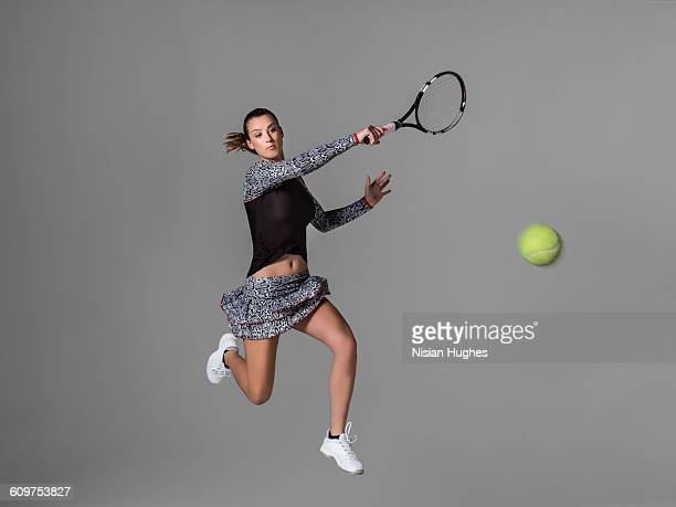 Young woman playing tennis hitting forehand