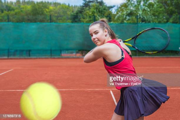 young woman playing tennis outdoors - val thoermer stock-fotos und bilder
