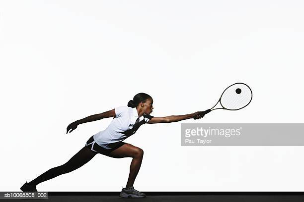 Young woman playing tennis, side view