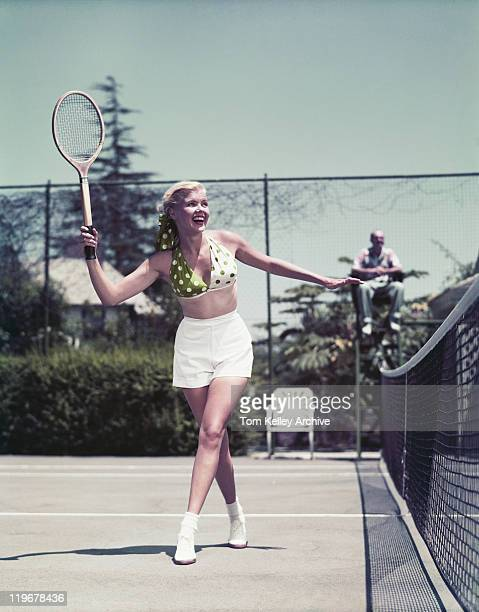 young woman playing tennis, smiling - archiefbeelden stockfoto's en -beelden
