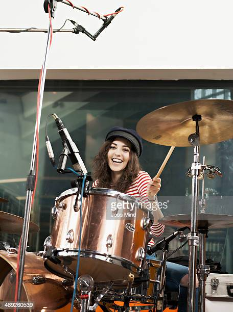 Young woman playing the drums, laughing