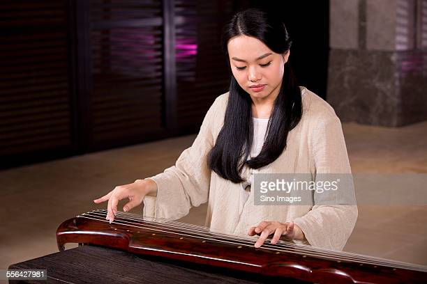young woman playing the guqin - stringed instrument stock pictures, royalty-free photos & images