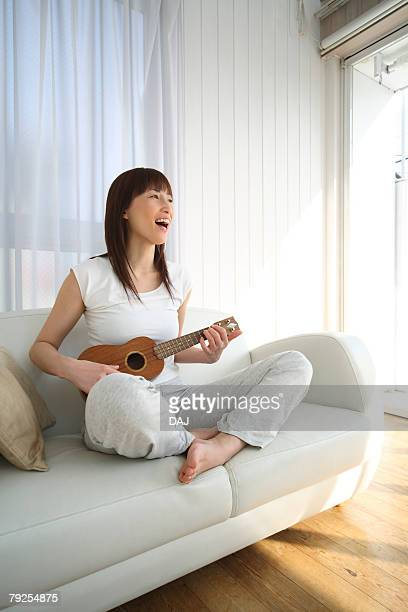 Young Woman Playing the Ukulele on Sofa, Side View