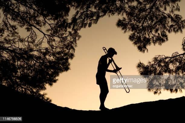 トロンボーンを弾く若い女性 - トランペット ストックフォトと画像
