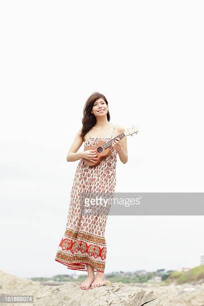 Young woman playing ukulele in beach