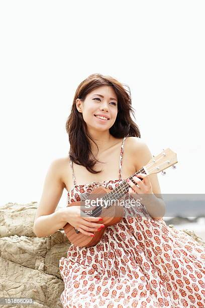 Young woman playing ukulele in beach,close up
