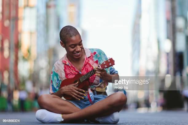 young woman playing ukulele in street - ukulele stock pictures, royalty-free photos & images