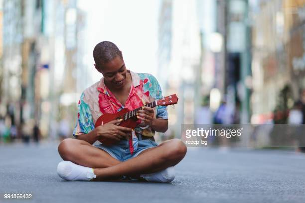 Young woman playing ukulele in street