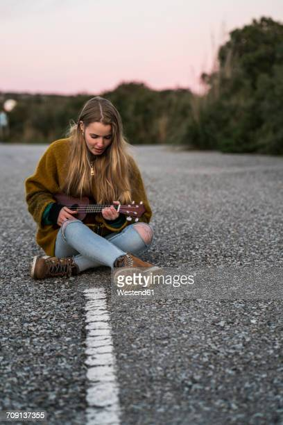 young woman playing ukulele on a road - liedermacher stock-fotos und bilder