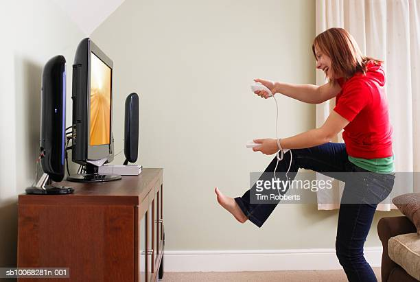 Young woman playing video game in living room, side view