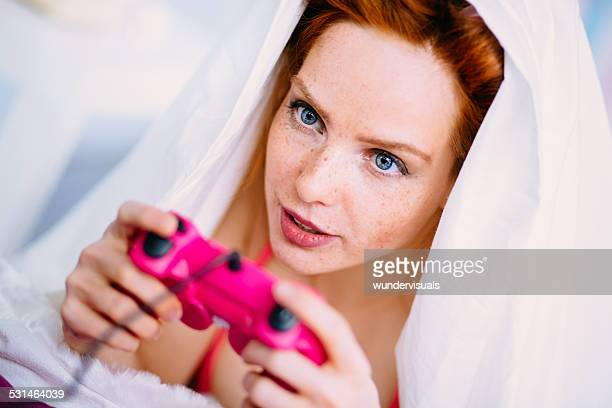 Mujer joven jugando videojuegos en la cama con sábanas