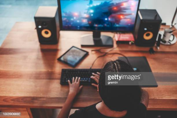 young woman playing video games on computer at home - gamer stock pictures, royalty-free photos & images