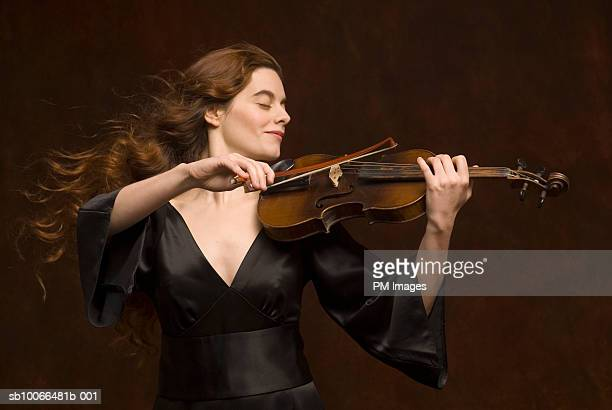 Young woman playing violin, eyes closed, smiling