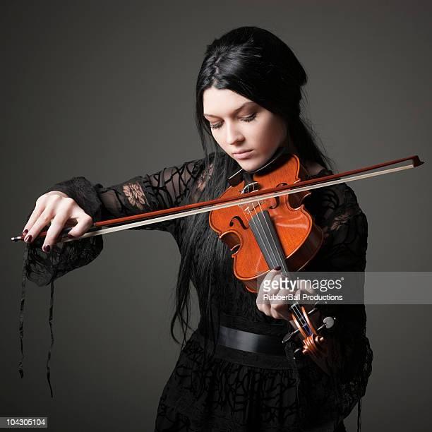 Jovem mulher a tocar violino