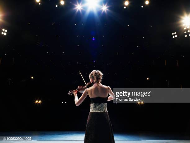 Young woman playing violin solo on stage, rear view