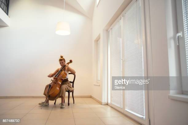 Young woman playing violoncello at home