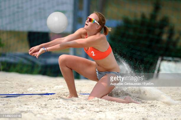 young woman playing volleyball at beach - strand volleyball stock-fotos und bilder
