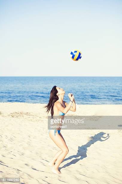 Jeune femme jouant au volley-ball sur la plage
