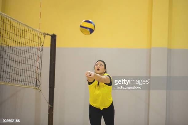 young woman playing volleyball - high school volleyball stock photos and pictures