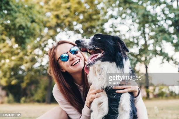 mujer joven jugando con un perro al aire libre - border collie fotografías e imágenes de stock