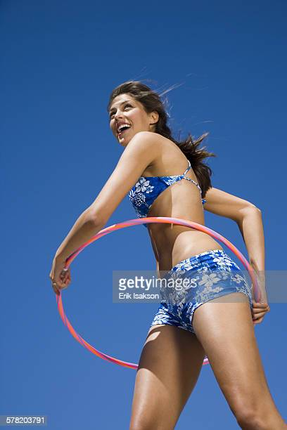 young woman playing with a hula hoop - vitalität stockfoto's en -beelden