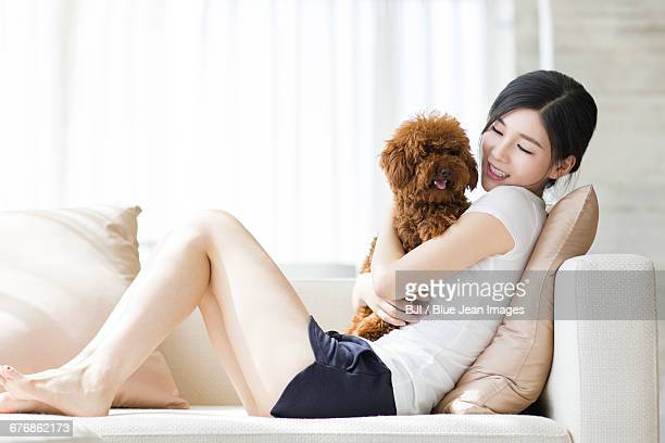 young woman playing with a pet poodle at home - short sleeved stock pictures, royalty-free photos & images
