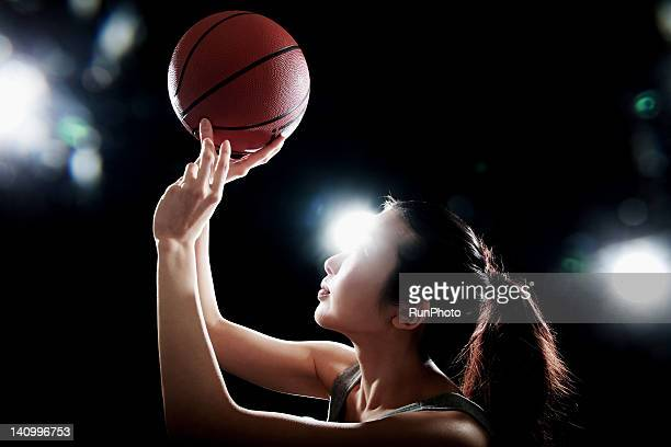 young woman playing with basketball