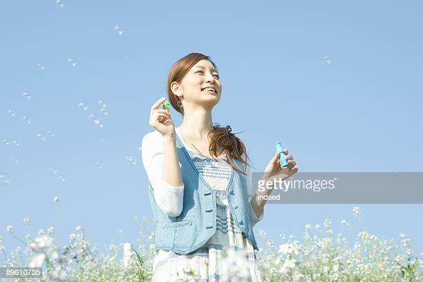 Young woman playing with bubbles on field
