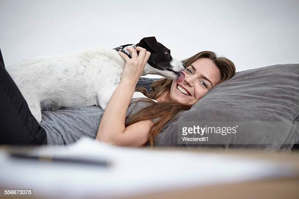 Young woman playing with dog on couch