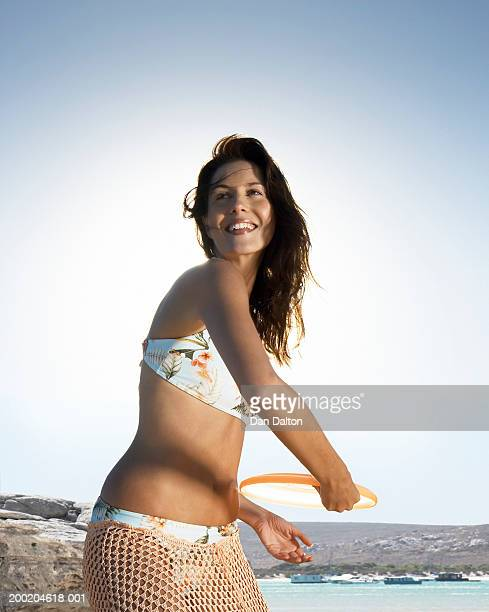 Young woman playing with flying disc on beach, smiling