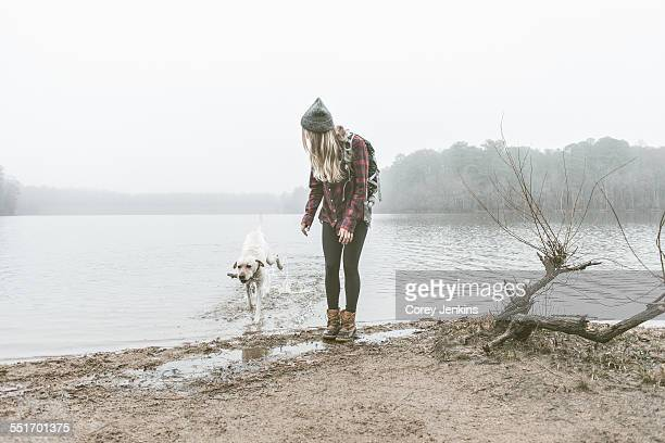 young woman playing with her dog on misty lakeside - cary stockfoto's en -beelden
