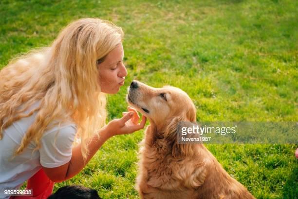 jeune femme jouant avec son chien en plein air. - représenter photos et images de collection