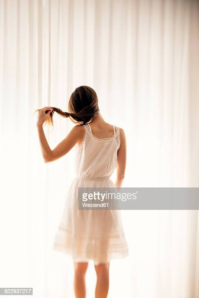 young woman playing with her hair in front of a white curtain, back view - women wearing see through clothing stock pictures, royalty-free photos & images