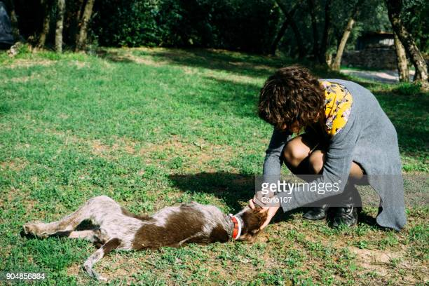 Young woman playing with her little dog