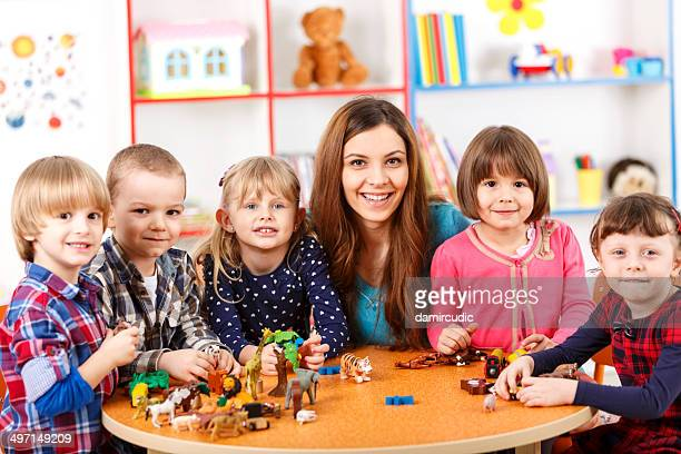 young woman playing with kids in nursery school - toy animal stock photos and pictures