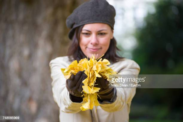 Young Woman Playing With Leaves In Park During Autumn