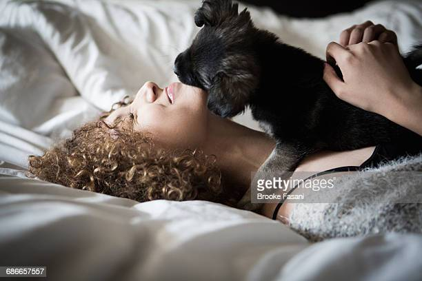 young woman playing with puppy - puppies stock pictures, royalty-free photos & images