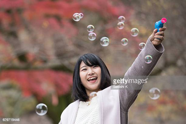 Young woman playing with soap bubbles in autumn foliage