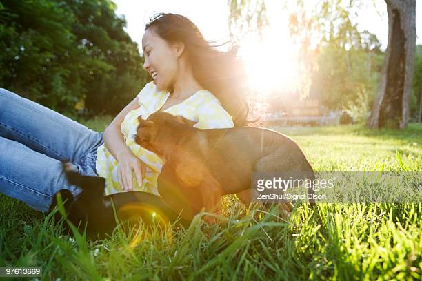 Young woman playing with two puppies outdoors