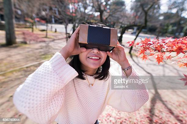 Young woman playing with virtual reality simulator in autumn foliage