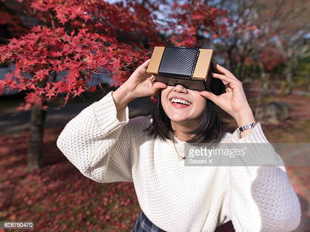 Young woman playing with virtual reality simulator in autumn leaves