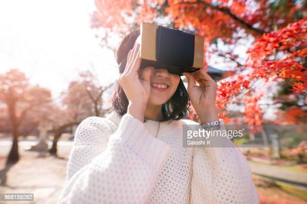 紅葉に仮想現実シミュレータを演奏若い女性