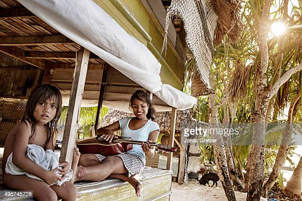A young woman plays a guitar in her house that is only about 2 meters from the sea in the village Eita The people of Kiribati are under pressure to...