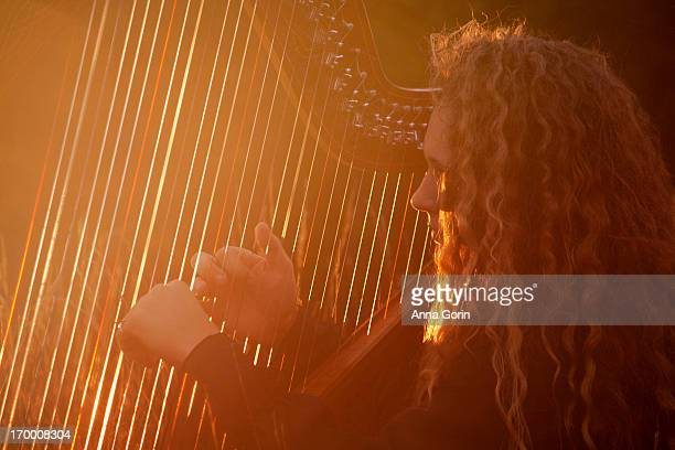 Young woman plays Celtic harp at sunset