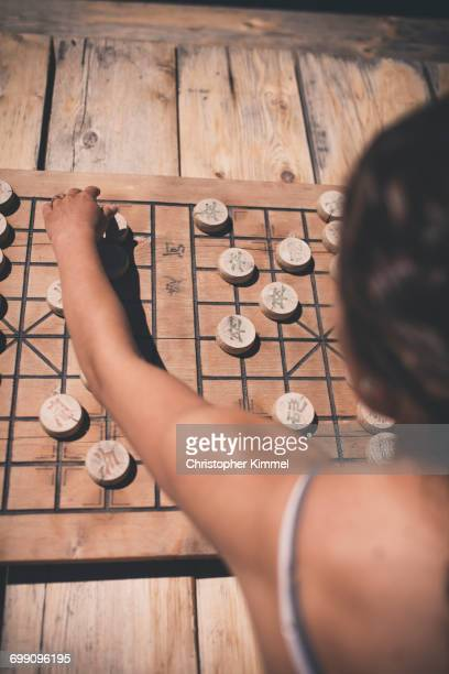 A young woman plays Chinese Chess.